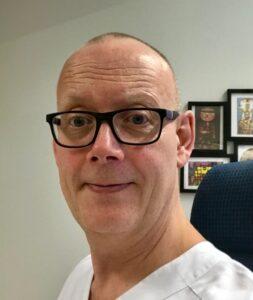Profilbild på Jan-Olof Malmborn. Jan-Olof bär svartbågade, fyrkantiga glasögon och vit skjorta.