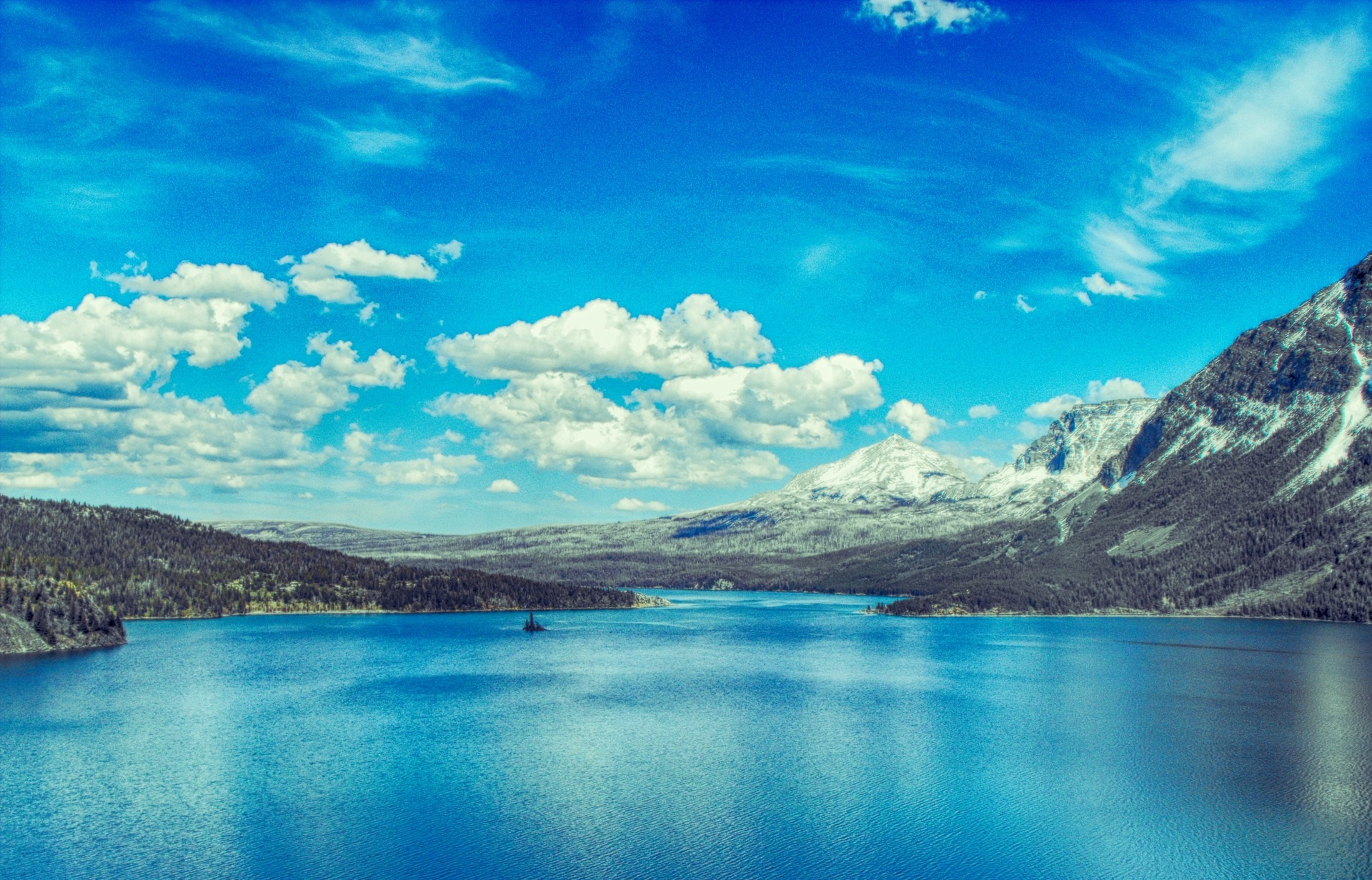 Blå sjö omgiven av vintriga berg.