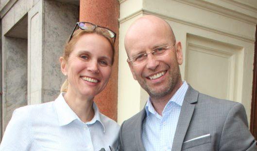 Kristina Klintö och Magnus Becker står utanför en byggnad och ler. Kristina har på sig vit skjorta samt glasögon uppskjutna på huvudet. Magnus har på sig blåvit skjorta och grå kavaj samt glasögon.