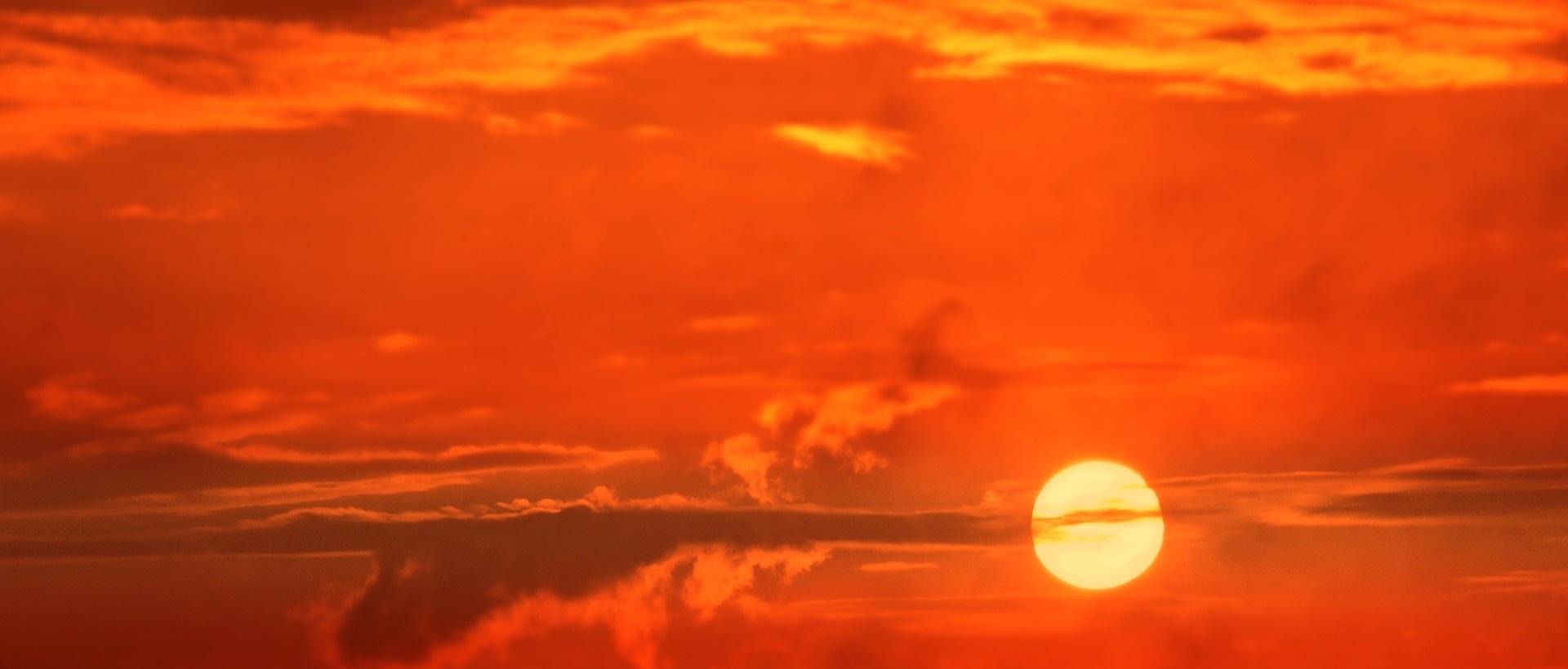 Solnedgång mot röd himmel.