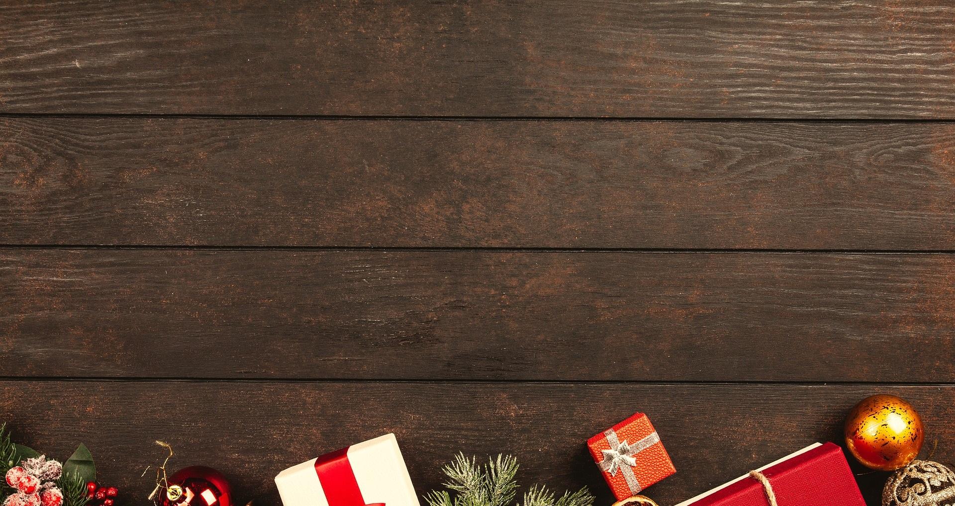 Juldekorationer (paket, kulor, granbarr med mera) mot bakgrund i form av mörka plankor.