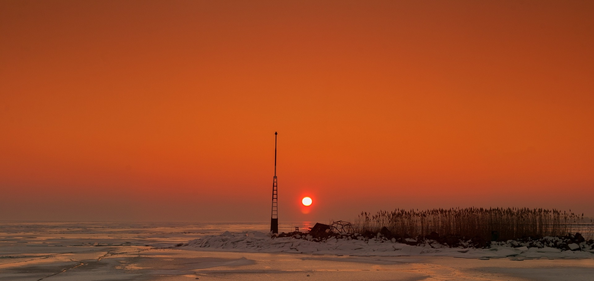 Solnedgång över fruset vatten. På en udde syns en antenn.