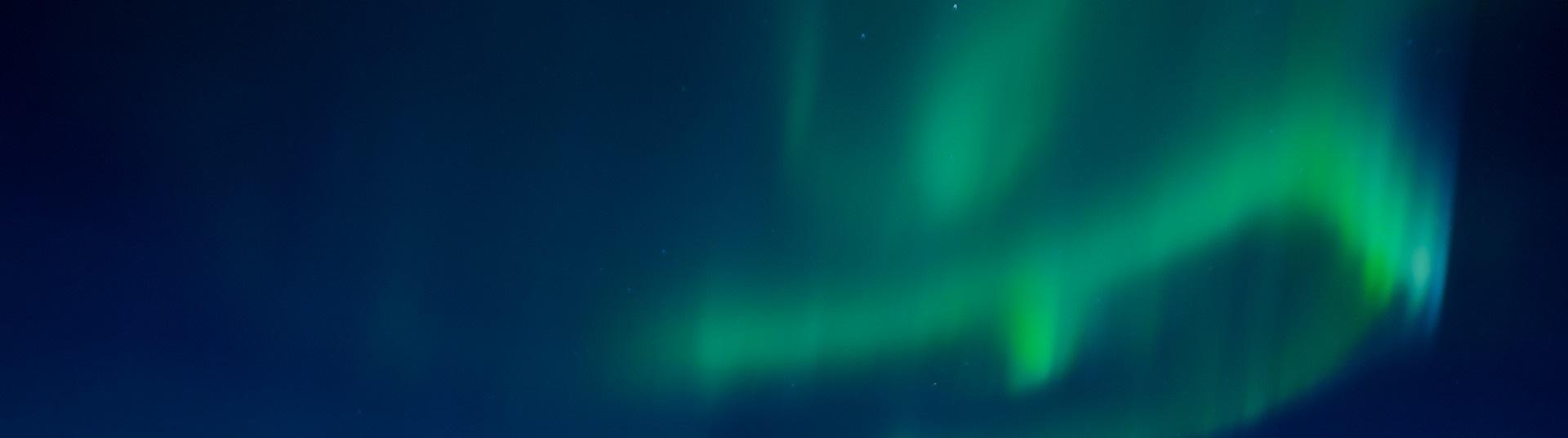Grönt norrsken mot mörkblå natthimmel.