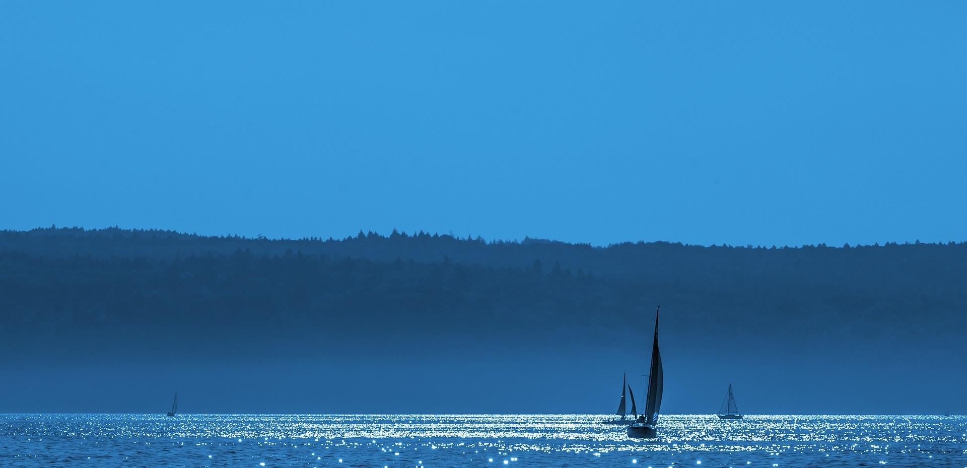 Blå bakgrundsbild, hav med segelbåtar.