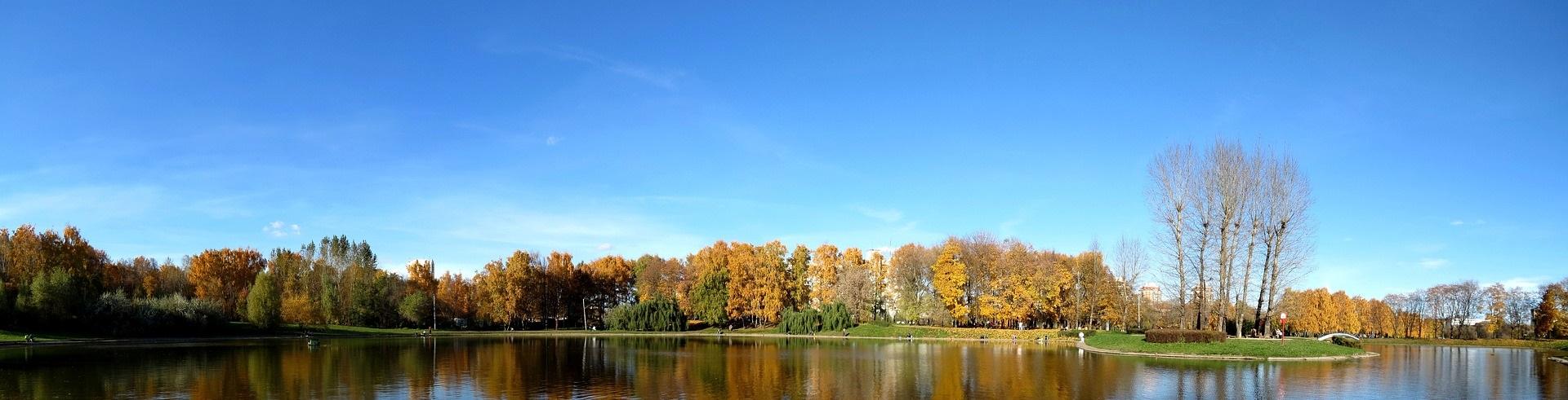 Blå bakgrundsbild, sjö och höstträd.
