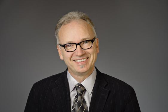 Anders Behndig iförd svartbågade glasögon, svart kavaj, vit skjorta och gråsvart slips.