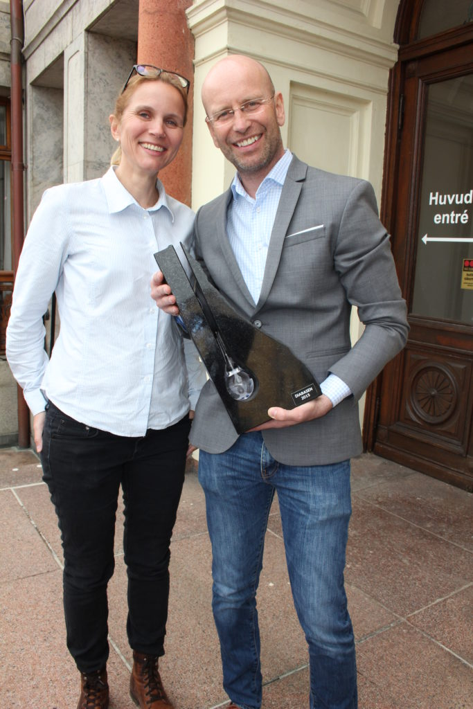 Kristina Klintö och Magnus Becker står utanför en byggnad och ler. Kristina har på sig vit skjorta och svarta byxor samt glasögon uppskjutna på huvudet. Magnus har på sig blåvit skjorta, grå kavaj, blåa jeans samt glasögon. Magnus håller i prisstatyett i mörk sten.
