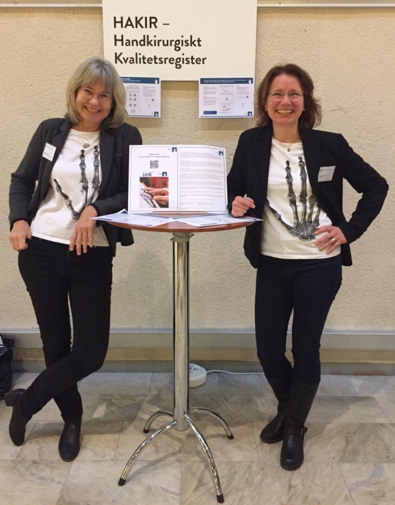Marianne Arner och Nina Lindblad. Marienne och Nina står på var sin sida om ett högt, litet runt bord och lutar sig mot detta. Båda har svarta kläder förutom en vit t-shirt med en skeletthand på som motiv. Båda bär glasögon och ler mot kameran.