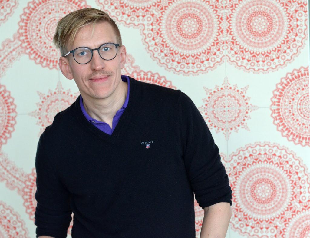 Anders Håkansson i profilbild iförd svart tröja och uppstickande lila krage. Anders bär även glasögon.