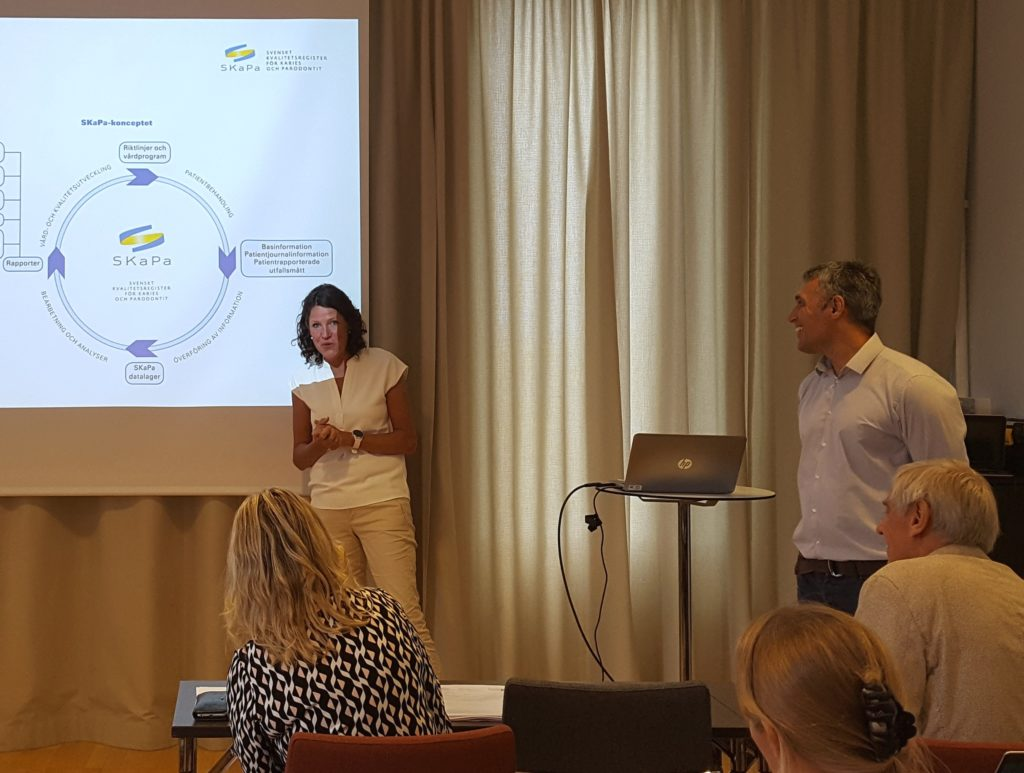 Ingela Kierkegaard Thudin och Michael Novak föreläser. Ingela står framför de bådas presentation och ler mot åhörarna. Ingela är klädd i vit topp och beigea byxor. Michael är klädd i vit skjorta och blåa jeans.