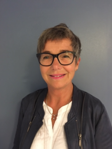 Fanny Franzén-Petersson i profilbild. Fanny bär svartbågade glasögon, vit skjorta och mörkgrå jacka. Fanny ler mot kameran.