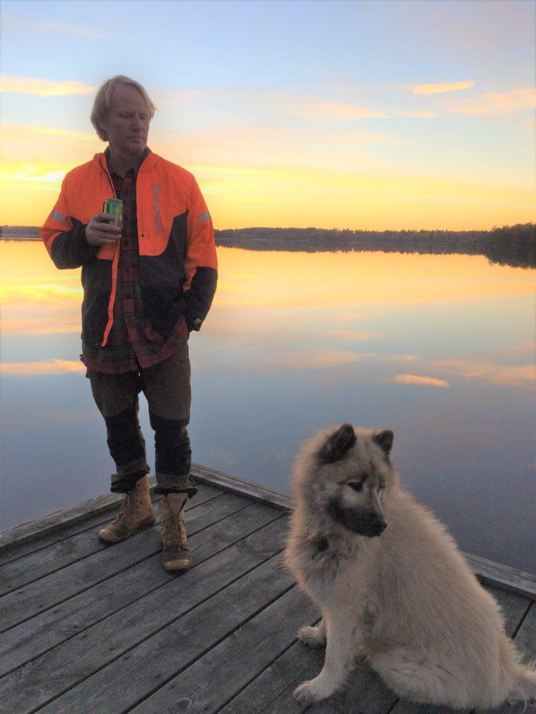 Bengt Söderberg står på en brygga vid en sjö i solnedgång. Bengt är klädd i orange jacka, rödrutig skjorta, beigea byxor och beigea skor. Till höger om Bengt på bryggan sitter en vit hund.