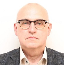 Profilbild på Åke Karlsson. Åke bär glasögon, vit skjorta och grå kavaj.
