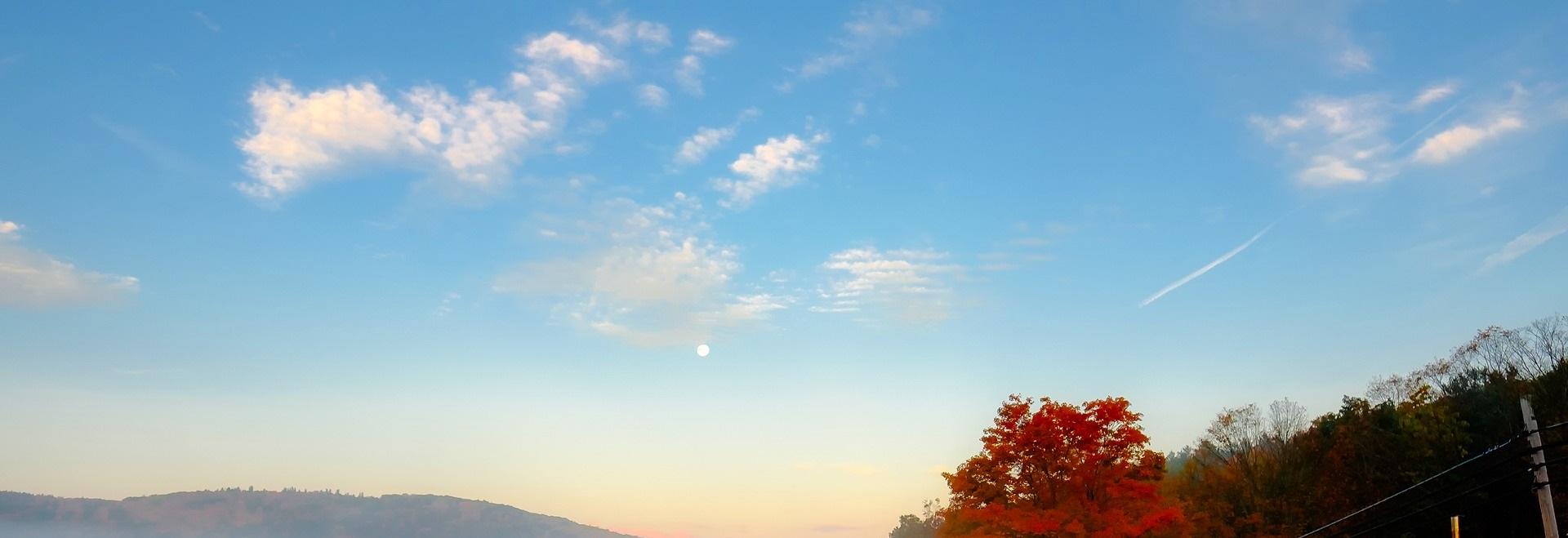 Blå himmel med några vita moln. I nederkanten syns bergskrön till vänster och ett höstfärgat träd till höger.