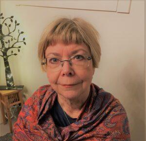 Profilbild på registerhållare Inger Westborg. Inger har kortklippt, blont hår, glasögon och bär en rödblå blus.