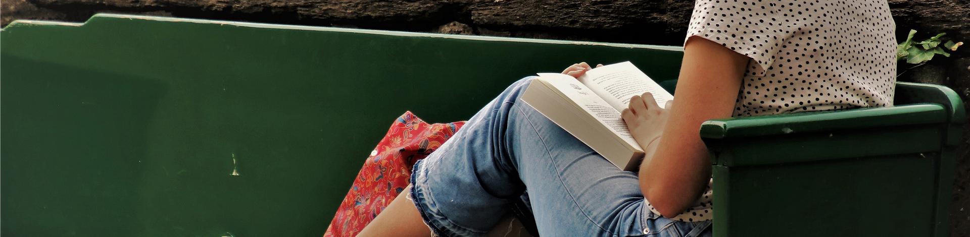 Kvinna som sitter på en grönparkbänk och läser en bok.