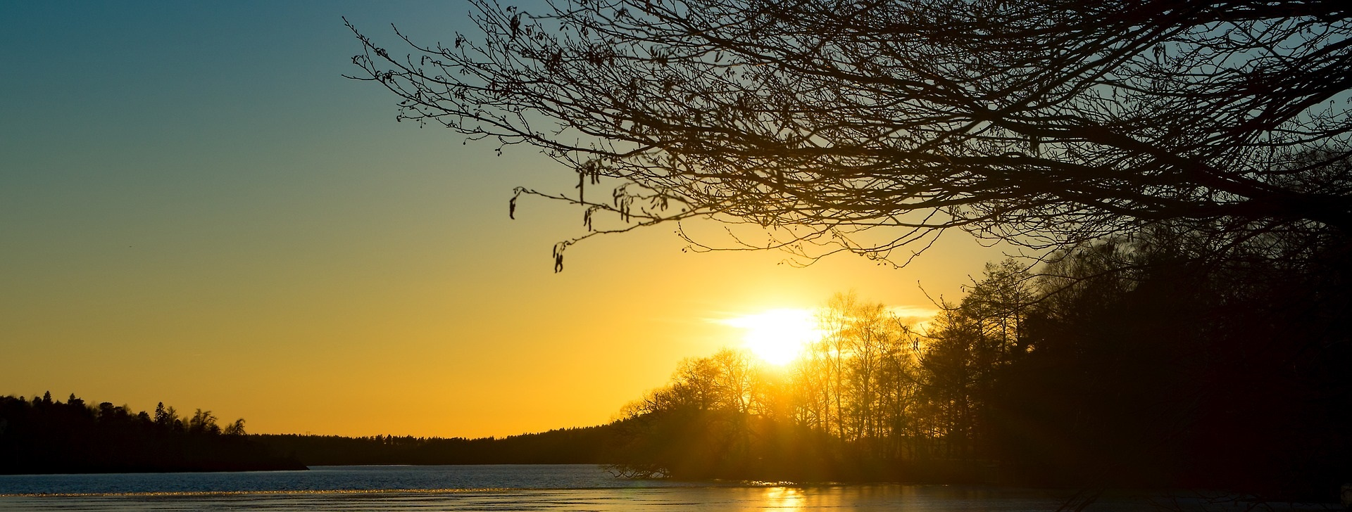 Solnedgång över skog och frusen sjö.