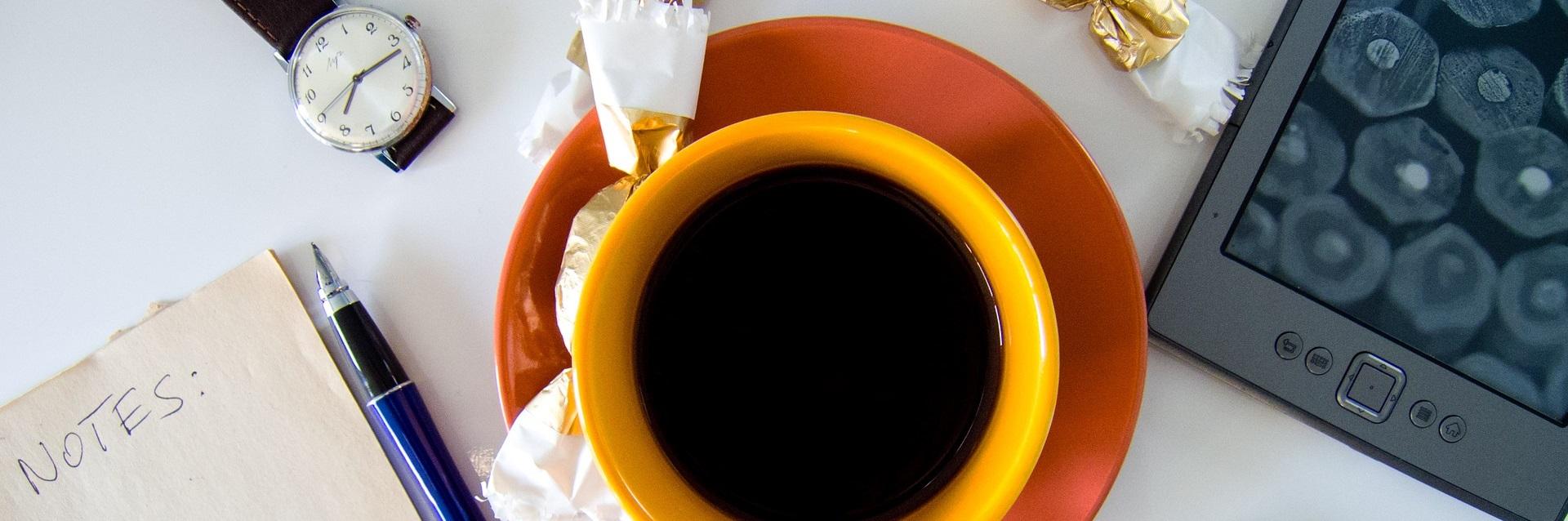 Bild tagen på ett bord ovanifrån. På bordet finns ett anteckningsblock, en blå penna, en gul kaffekopp på orange fat, ett armbandsur, guldpappersinslagna godisbitar samt en svart mobiltelefon.