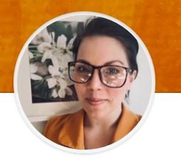 Kim Scharafinski framför tavla med blommotiv. Kim kan ses bära glasögon och orange kavaj.