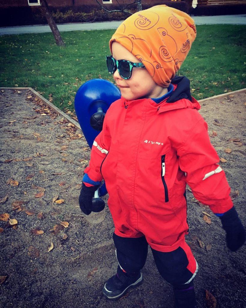 Miles Scharafinski står utomhus i sandlåda. Miles har på sig orange mössa, blåbågade glasögon, röd overall och svarta skor.