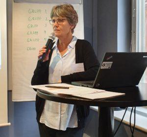 Anna-Karin Öhman. Anna-Karin har kort, ljust hår och bär svartbågade glasögon, ljus skjorta och svart tröja.