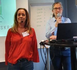 Sara Andersson och Lotta Edman. Sara har axellångt ljust hår, röd tröja och namnskylt. Lotta har hästsvans, svartbågade glasögon och ljusblå skjorta. Lotta håller i en mikrofon.