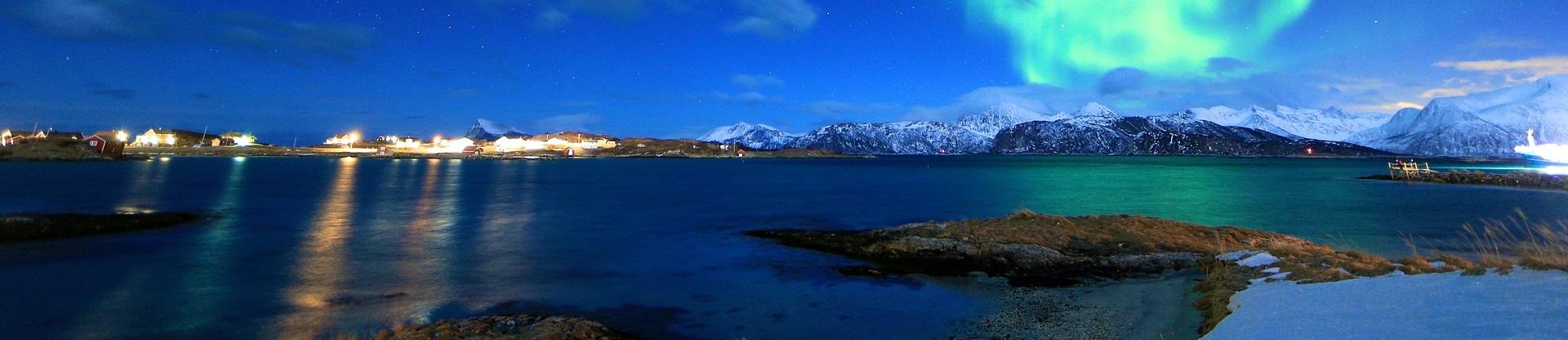 Vinterkall kväll med norrsken över insjö. I horisonten syns en fiskeby till vänster och en snötäckt bergskedja till höger..