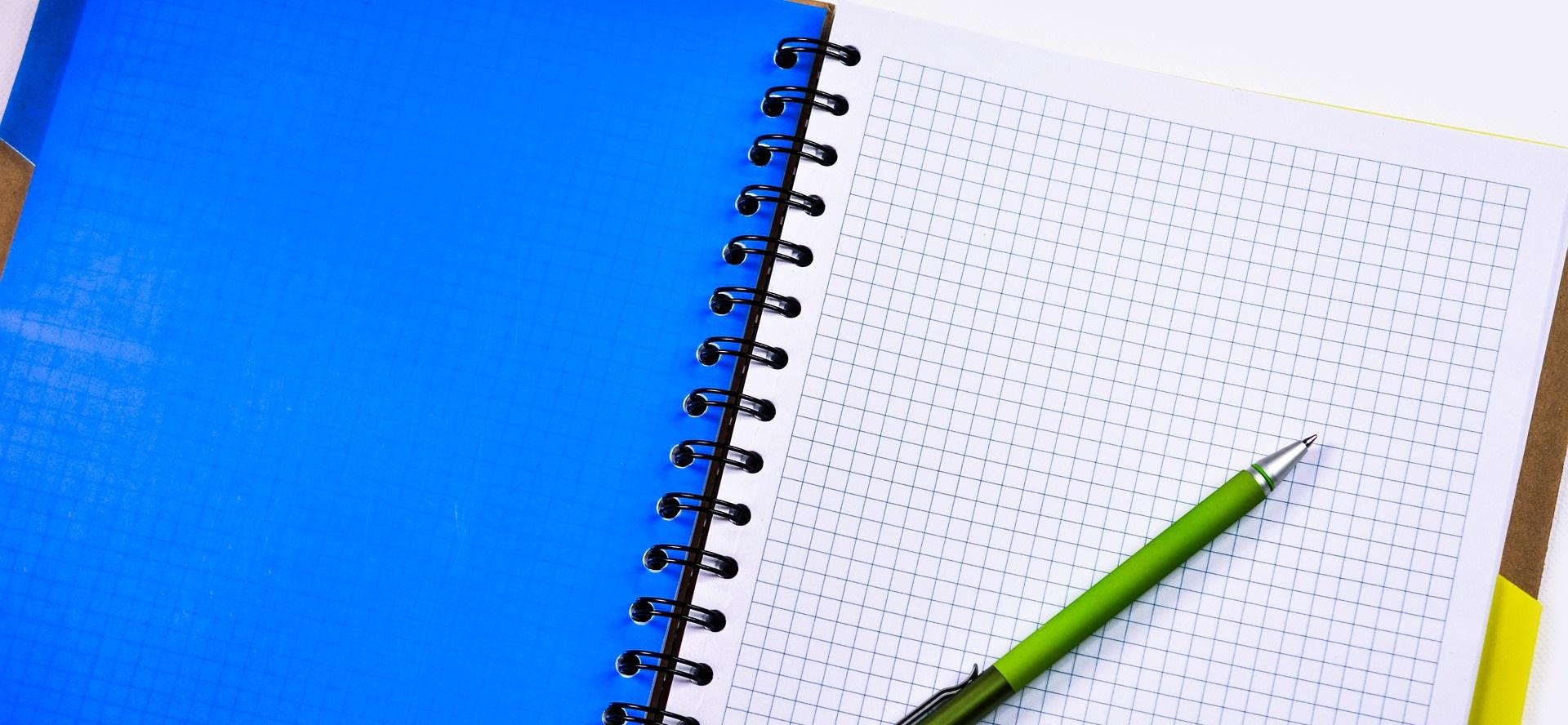 Blå anteckningsbok med grön penna.