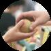 Hand som ger annan hand ett äpple.